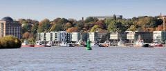 Blick von der Süderelbe / Köhlbrand zum Elbrand Neumühlen, Stadtteil Ottensen - Perlenkette der Norderelbe, Bürogebäude erbaut ab 2000. Schlepper liegen am Ponton in der Elbe - der Altonaer Elbhang ist mit Bäumen in Herbstfarben bedeckt.
