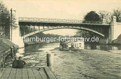 Zwei Jungen sitzen auf dem Anleger Winterhuder Fährhaus - ein Alsterdamper hat gerade abgelegt und fährt unter der Hochbahnbrücke Richtung Aussenalster.