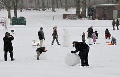 Winter im Hamburger Stadtpark - Kinder und Väter bauen einen Schneemann am Planschbecken.