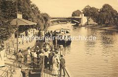 Anleger Winterhuder Fährhaus an der Alster - Menschen, Fahrgäste warten auf den Alsterdampfer - im Hintergrund die Hochbahnbrücke der Hamburger Hochbahn.