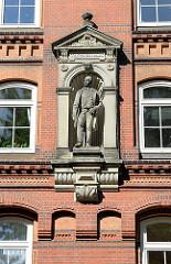 Stifterfigur Abraham Philipp Schuldt an der Hausfassade der STiftswohnungen in der Hamburger STrasse Hütten, Stadtteil Neustadt.