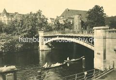 Historisches Motiv aus Hamburg Winterhude - Hudtwalckerstrassenbrücke über die Alster, Kanus fahren auf dem Hamburger Fluss - im Hintergrund das Gemeindehaus der Eppendorfer St. Johanniskirche.
