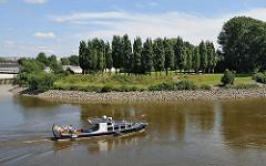 Ein Sportboot / Motorboot kommt vom Oberhafenkanal und fährt in die Norderelbe ein - im Hintergrund der Elbpark Entenwerder mit den in einer Rundung 2007 bei der Gestaltung der Grünanlage neu angegepflanzten Pappeln. Das Ufer ist mit Steinen ge