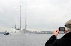 Die Segelyacht White Pearl kehrt von einer  Probefahrt in den Kieler Hafen zurück; ein Tourist fotografiert mit seinem Handy / smartphone die Szene.