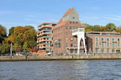 Blick von der Elbe auf den Altonaer Kaispeicher, erbaut 1924 - historische Hamburger Industriearchitektur im Altonaer Hafen, Stadtteil Ottensen - dahinter Bäume mit Herbstlaub, Neubau mit Wohnungen.