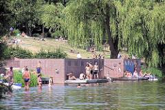 Sommer im Hamburger Stadtpark - BesucherInnen sonnen sich oder baden im Stadtparksee.