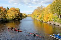 Blick von der Streekbrücke auf die Alster in Hamburg Winterhude / Eppendorf - Herbstbäume am Ufer, Ruderboote fahren Richung Isebekkanal.