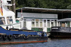 Ehemalige Zollschiffstation in Hamburg Rothenburgsort / Entenwerder; die Aufschrift ist von der Holzbaracke abmontiert. Der Ponton an der Norderelbe wird als Schiffsliegeplatz von Arbeitsschiffen genutzt.
