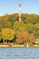 Herbstbäume mit goldgelben und rotbraunen Herbstblättern am Elbufer; ein Segelboot kreuzt auf der Elbe; Leuchtturm / Leuchtfeuer zwischen den Bäumen.