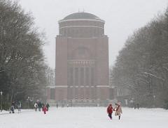 Schneefall im Winter im Hamburger Stadtpark - Kinder spielen auf einer Wiese vor dem Planetarium.
