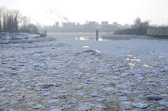 Winter in Hamburg - Eisschollen auf der Elbe. Blick über Einfahrt zum Billehafen / Oberhafenkanal zur Norderelbe - lks. die kahlen Bäume vom Elbpark Entenwerder. Am gegenüber liegenden Elbufer im Dunst die Industrie auf der Veddel.