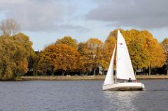 Weisses Segelboot auf der Aussenalster - Parkanlage mit Herbstbäumen an der Aussenalster in Hamburg Uhlenhorst - Areal des ehem. Uhlenhorster Fährhaus.