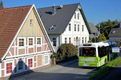 Alte Wohnhäuser am Estedeich in Hamburg Cranz - ein Hybridbus der HVV fährt am Estedeich.