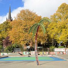 Park Fiction / Antonipark / Gezi Park in Hamburg St. Pauli - Eisenpalme, herbstliche Bäume, Kirchturm der St. Pauli Kirche.