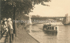 Historisches Motiv der Hamburger Alster - Alsterdampfer und Hochbahnbrücke in Hamburg Winterhude; Frauen mit Hüten stehen am Zaun beim Anleger Winterhuder Fährhaus.