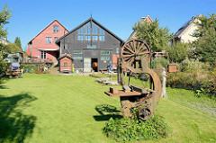 Aussenansicht der  Bootswerft Cranz - von 1868 bis 1992 wurden in jetzt unter Denkmalschutz stehenden Bootshalle Kähne und Beiboote aus Holz gefertigt. Eine alte Bandsäge steht als Dekoration auf der Wiese an der Este.
