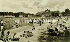 Badeanstalt am Stadtparksee - Kinder sitzen im Sand beim Freibad an der Stadthalle im Hamburger Stadtpark.