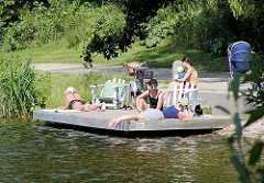 Sommer im Hamburger Stadtpark - BesucherInnen sonnen sich am Stadtparksee.