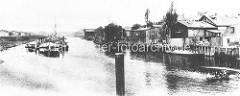 Historisches Foto vom Hafenbecken in  Hamburg Rothenburgsort - Lastkähne liegen an Dalben im Wasser; Gewerbegebäude sind direkt an die Wasserseite gebaut / Schiffe werden an der Kainalage entladen.