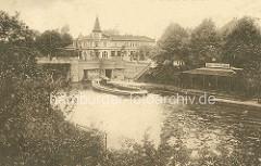 Altes Foto vom Anleger Winterhuder Fährhaus mit Wartehäuschen aus Holz und Alsterdampfer - im Hintergrund das Winterhuder Fährhaus.