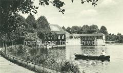 Blick vom Rundweg am Stadtparksee in Hamburg Winterhude - ein Kanu dümpelt auf dem Wasser - Parkcafé am Seeufer.