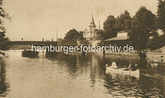 Historisches Foto vom Anleger Winterhuder Fährhaus mit Wartehäuschen aus Holz und Alsterdampfer und Kanu - im Hintergrund das Winterhuder Fährhaus.