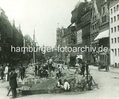 Baustelle am Rödingsmarkt, Kinder spielen im Sand - Bauarbeiter arbeiten an dem Hochbahnviadukt für die Hamburger Hochbahn. Karren und Pferdewagen stehen am Strassenrand.