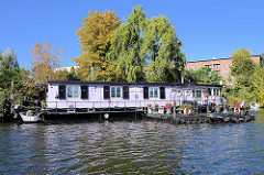 Hausboot und Herbstbaum an der Bille in Hamburg Hamm.