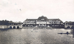 Blick über den Stadtparksee im Hamburger Stadtpark zur Stadthalle - Kanus und Ruderboote auf dem Wasser.