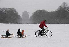 Winterzeit in der Hansestadt Hamburg - ein Vater zieht mit dem Fahrrad zwei Schlitten mit Kindern durch den Schnee im Stadtpark.