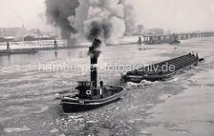Historisches Foto von der Norderelbe im Winter - Eisschollen treiben auf dem Wasser, ein Schlepper unter Dampf zieht einen Oberländer Kahn. Im Hintergrund die Zollstation Entenwerder - niedrige Lagerhäuser am Zollhafen, dahinter Wohnblocks von