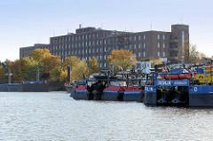 Blick über den Peutehafen auf der Veddel - re. Schubschiffe am Ufer, im Hintergrund die Industriearchitektur / Klinkergebäude der ehem. GEG an der Peutestrasse.