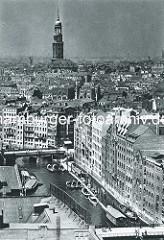 Historischer Blick über das Nikolaifleet der Altstadt Hamburgs - im Vordergrund die Reimersbrücke, in der Bildmitte die Holzbrücke. Barkassen und Arbeitsschiffe liegen an einem Steg - im Hinterrund ragt der Kirchturm der St. Michaeliskirche auf.