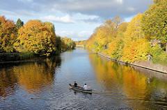 Blick von der Streekbrücke auf die Alster in Hamburg Winterhude / Eppendorf - Herbstbäume am Ufer, ein Kanu fährt Richung Isebekkanal.