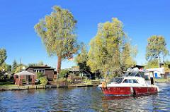 Schrebergärten / Kleingarte an der Bille in Hamburg Hamm, ein Motorboot fährt auf dem Hamburger Fluss.