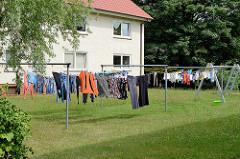 Trockenplatz auf der Wiese - Wäsche ist auf der Leine zum Trockenen aufgehängt - einstöckiger Wohnblock, Reinbek / Kreis Stormarn.