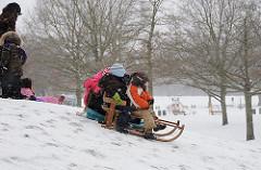 Winter im Hamburger Stadtpark - Kinder rodeln an einem kleinen Berg.