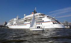 Kreuzfahrtschiff / Passagierschiff EUROPA bei der Hamburger Überseebrücke im Hafen Hamburgs; ein Segelboot segelt auf der Elbe - blauer Himmel.