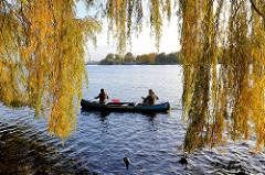 Blick durch die herabhängenden Weidenzweige auf die Aussenalster in Hamburg Winterhude an der Bellevue - ein Kanu fährt auf dem Wasser in der Herbstsonne.