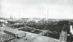 Historisches Motive aus dem Hamburger Petroleumhafen in Waltershof - Petroleumfässer, Ölfässer liegen an Land - am Steg das Frachtschiff Phoebus; im Hintergrund Tankanlagen.
