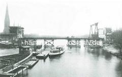 Bau der Hochbahnbrücke über den Mundsburger Kanal / Kuhmühlenteich; Baugerüste an den Brückenpfeilern, ein Alsterdampfer hat am Ponton angelegt - im Hintergrund der Kirchturm der 1886 eingeweihten St. Gertrud Kirche in Hamburg Uhlenhorst.