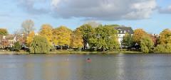 Blick über die Aussenalster zur Strasse Bellevue in Hamburg Winterhude - Spaziergänger unter Herbstbäumen, ein rotes Kajak auf der Alster.