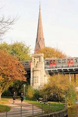 Brückenpfeiler der Kühmühlenbrücke in Hamburg Uhlenhorst - ein Hochbahnzug überquert die Brücke, dahinter der Kirchturm der St. Gertrudkirche.