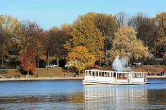 Der Alsterdampfer St. Georg fährt in die Hamburger Binnenalster ein - im Hintergrund Herbstbäume an der Promenade an den Lombardsbrücken. Das Alsterdampfschiff St. Georg ist das älteste noch fahrtüchtige Dampfschiff Deutschlands und wurde 1876 auf de
