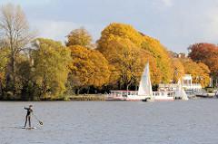 Blick über die Aussenalster ins herbstliche Hamburg Uhlenhorst - goldener Herbst mit prächtig gefärbten Bäumen an der Aussenalster beim ehem. Uhlenhorster Fährhaus - Segelboote und Stand Up Paddler auf der Alster.