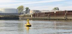 Blick in den Hamburger Petroleumhafen, Öltanks am Ufer - Signaltonne, Sondertonne Sperrgebiet - gelbe Tonne mit rotem Kreuz und gelbes Kreuz als Topzeichen - Durchfahrt verboten, das Gebiet darf nicht befahren werden.