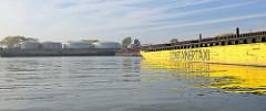 Hafenbecken Petroleumhafen im Hamburger Hafen - ein gelber Leichter mit der Aufschrift Containertaxi liegt an der Spundwand, am Ufer Öltanks.