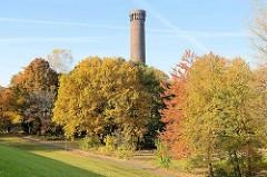 Herbst im Traunspark von Hamburg Rothenburgsort - hinter den Bäumen mit Herbstlaub der historische Wasserturm der Wasserwerke.
