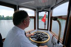 Kapitän am Steuerrad vom Alsterdampfer St. Georg auf dem Hamburger Stadtparksee. Das Alsterdampfschiff St. Georg ist das älteste noch fahrtüchtige Dampfschiff Deutschlands und wurde 1876 auf der Reiherstiegwerft in Hamburg gebaut. Seit 1994 verkehrt