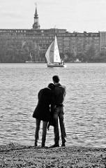 Paar stehend am Alsterufer - Segelboot unter Segeln auf der Hamburger Aussenalster; im Hintergrund der Kirchturm der  Heiligen Dreieinigkeitskirche in Hamburg St. Georg.
